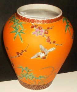 This is a vase that was converted to a flower pot. The orange is like a biscuit texture, flat.  It is just a wonderful color and the greens and red are a translucent painted enamel