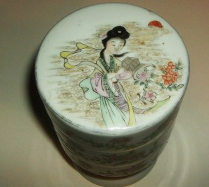 Stacked porcelain Chinese container with on a footed pedestal stand. Chinese maiden with bamboo insect observer.